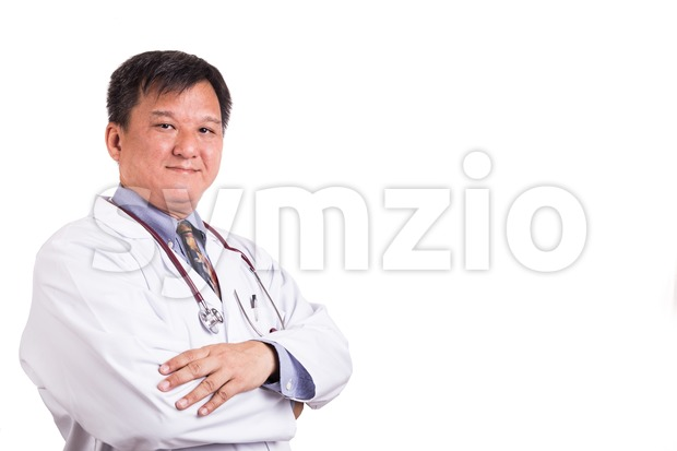 Confident matured Asian doctor with folded arms Stock Photo