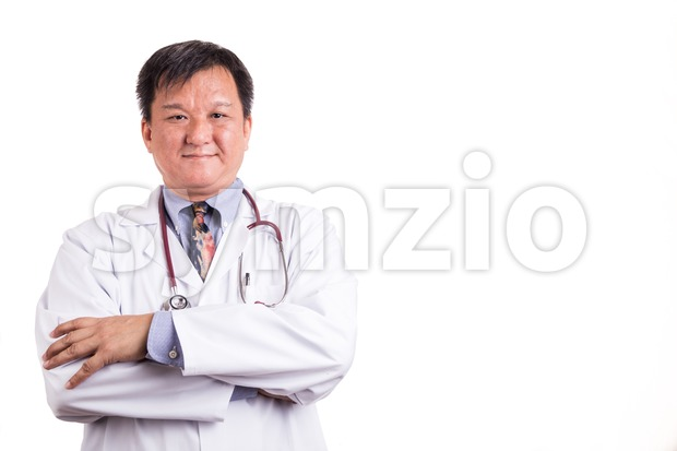 Confident matured Asian doctor with folded arms on white background