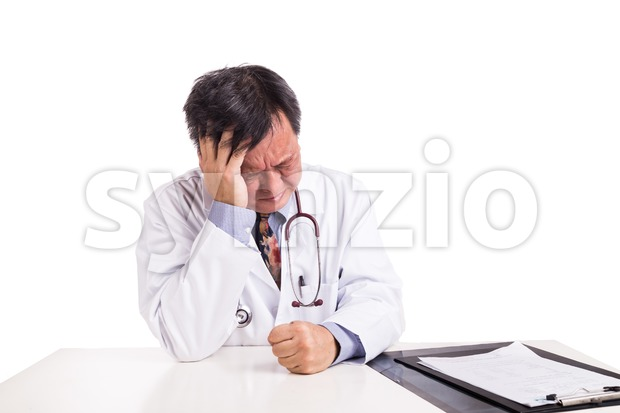 Depressed sad matured Asian doctor seated behind desk Stock Photo