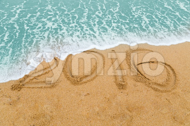 2016 inscription on sandy beach washed off with approaching wave Stock Photo