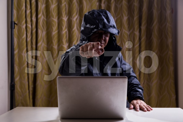 Angry Asian hacker pointing finger to audience while hacking network Stock Photo