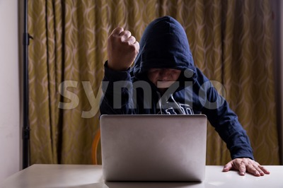 Asian hacker show fist while hacking computer network Stock Photo