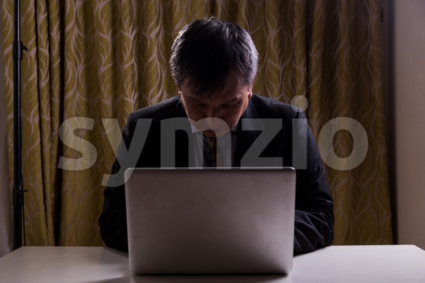 Asian businessman in suit attempting to hack computer network Stock Photo