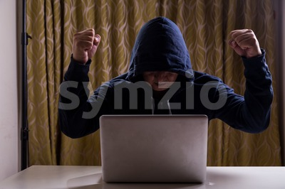 Asian hacker raise hands after successful hacked into network Stock Photo