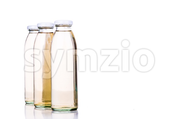 Translucent liquid in glass bottle on white background Stock Photo