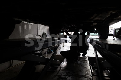 Silhouette of mechanics repairing car at small workshop garage Stock Photo