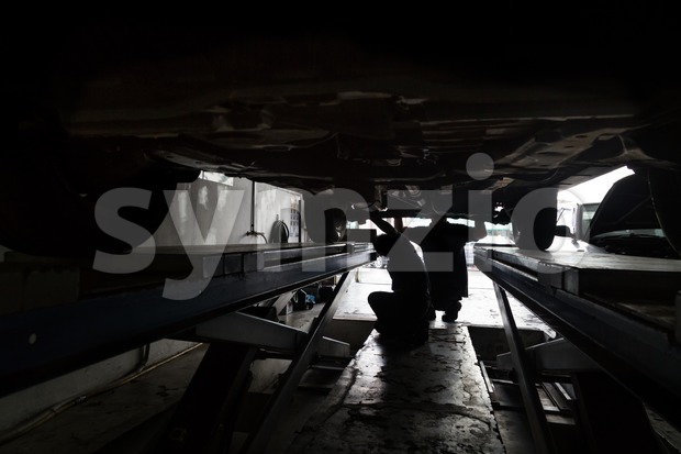 Silhouette of mechanics reparing car at small workshop garage Stock Photo