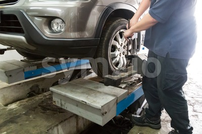 Mechanic fixing car aligner onto car wheel Stock Photo