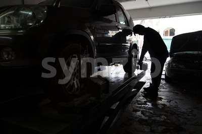 Silhouette of mechanic fixing car aligner onto car wheel Stock Photo