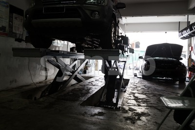 Silhouette of small workshop garage with two vehicles Stock Photo