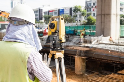 Engineer reviewing the dumpy automatic level instrument readings construction site Stock Photo
