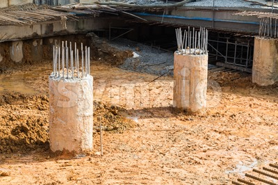 Concrete pillar with steel rods on dirt ground construction site Stock Photo
