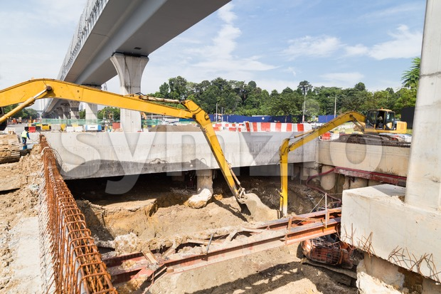 Excavators digging ground in construction of tunnel underpass in city Stock Photo