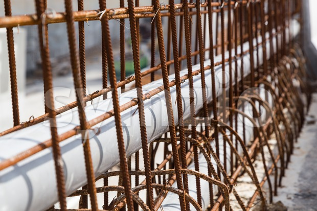 Closeup PVC pipes lined within rebar concrete divider road construction Stock Photo