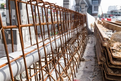 PVC pipes lined within rebar concrete divider in road construction Stock Photo
