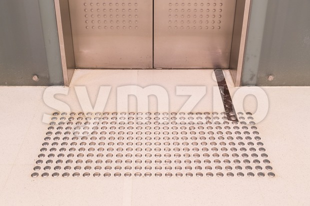 Tactile paving foot path for the blind entrance of elevator Stock Photo