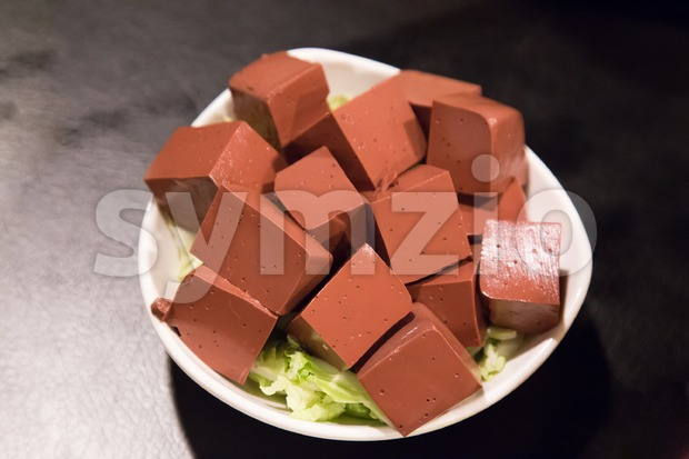 Plate of hardened pig blood in cubes, delicacy among Chinese Stock Photo
