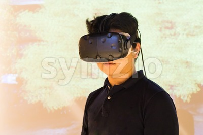 Asian teenager experiencing VR virtual reality entertainment gadget Stock Photo
