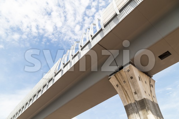Closeup perspective view of modern elevated rail transit infrastructure against blue sky