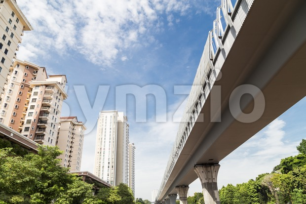 Perspective of modern high rise apartment with elevated rail line Stock Photo