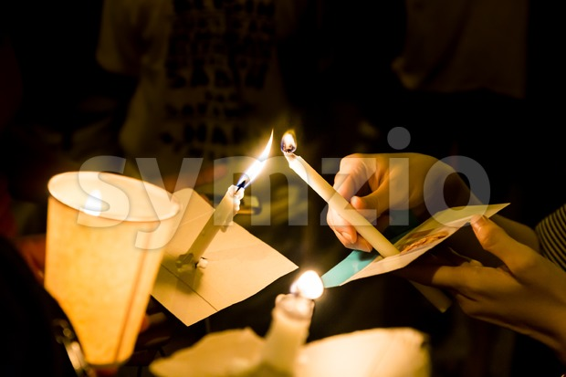 People lighting candle vigil in darkness seeking hope, worship, prayer Stock Photo