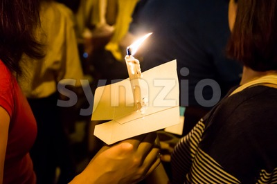 People holding candle vigil in darkness seeking hope, worship, prayer Stock Photo