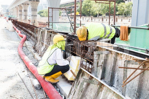 Two workers fitting wooden mould onto rebar at construction site Stock Photo