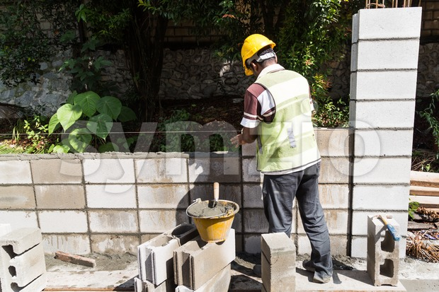 Workers constructing building erecting noise barrier walls at busy highway road