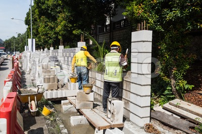 Workers constructing building noise barrier walls at busy highway Stock Photo