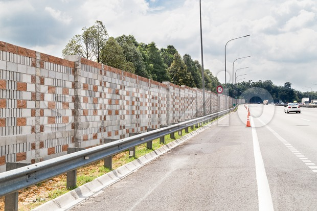 Concrete noise barrier wall along busy noisy highway insulate surrounding residential area