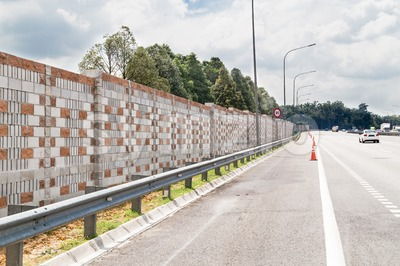 Concrete noise barrier wall along busy noisy highway Stock Photo