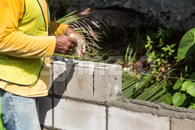 Worker inserting noise proofing sponge into barrier bricks during construction Stock Photo