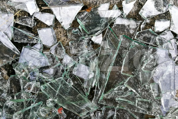 Heap of sharp shattered pieces broken glass on ground Stock Photo