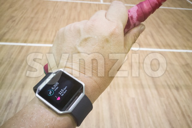 Perspective view of person reading watch with heart tracker during exercise