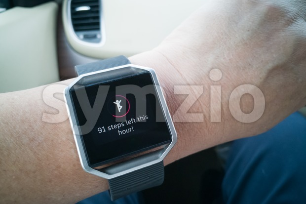 Perspective view of person reading wrist watch with heart and steps tracker while driving