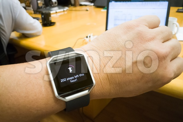 Perspective view of person reading wrist watch with heart and steps tracker in office working