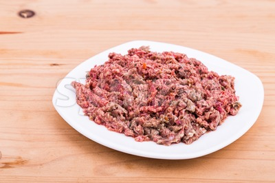 Fresh and nutritious minced raw meat dog food on plate Stock Photo