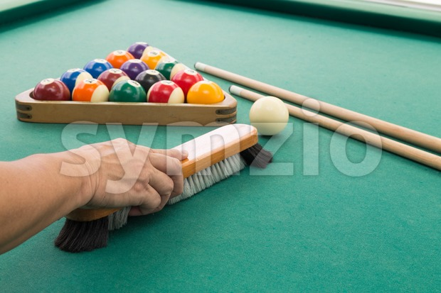 Hand brushing surface of green snooker pool billards table with balls and cue