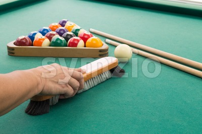 Hand brushing snooker pool billards table with balls and cue Stock Photo