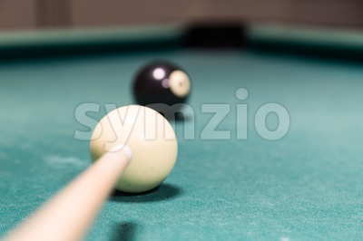 Focus on cue aiming black ball into snooker billards pocket Stock Photo