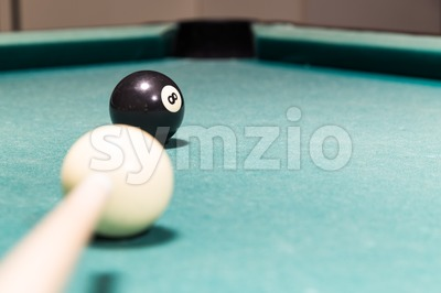 Cue aiming black ball into snooker billards table pocket Stock Photo