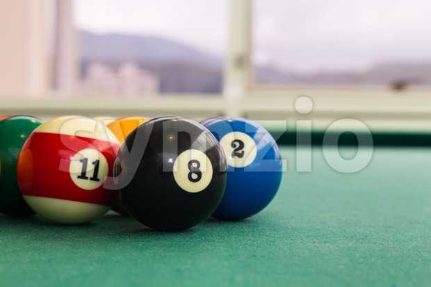 Closeup on snooker pool billards ball on table with green surface