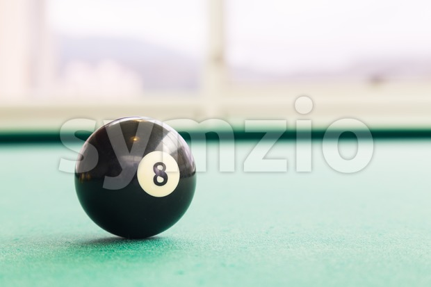 Closeup black snooker billards ball on table with green surface Stock Photo
