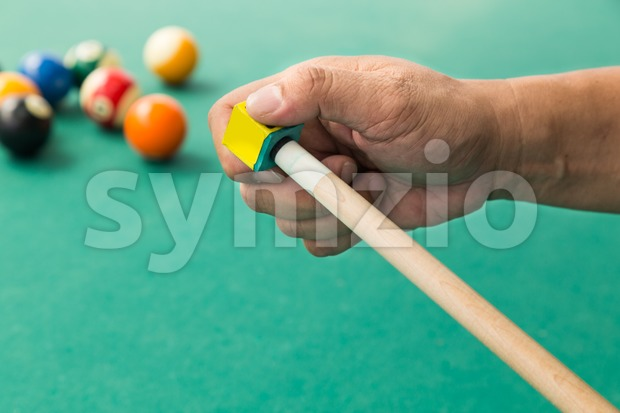 Hand applying chalk on tip of billards pool stick Stock Photo