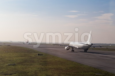 Commercial airplane queue taxiing to take off on runway Stock Photo