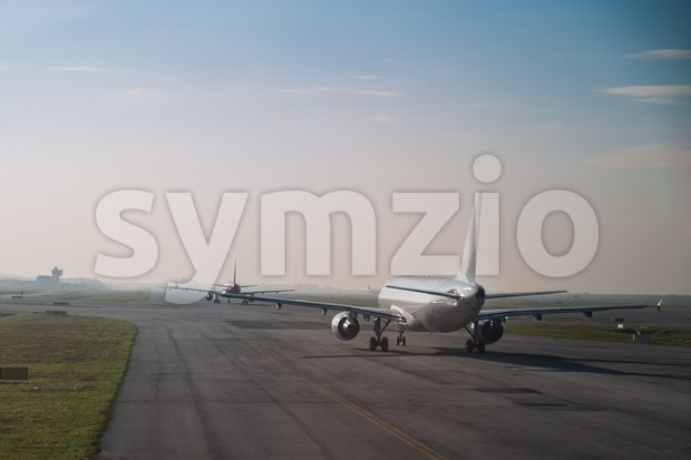 Commercial airplane queue and taxiing on tarmac to take off on runway