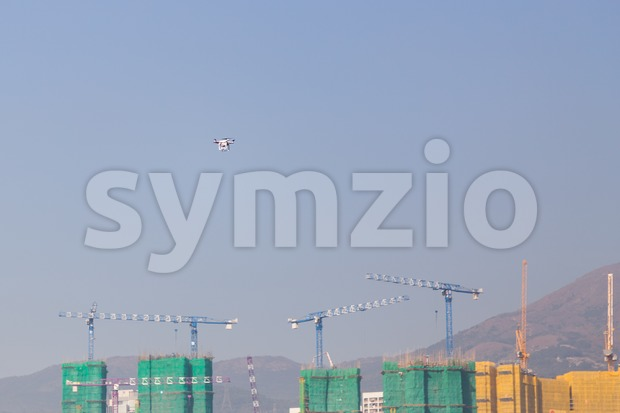 Drone doing surveillance take aerial photographs over cityscape Stock Photo