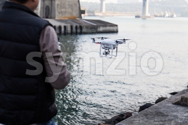 Person controlling drone remotely with device flying over river