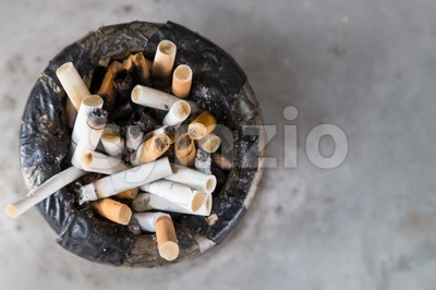 Overhead view of dirty cigarette butts in ash tray Stock Photo