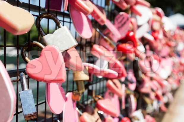 Closeup on pink love locks hanging on wire mesh with space for copies. Denotes romance and relationship security